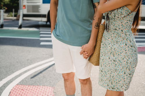Couple holding hands while standing on sidewalk