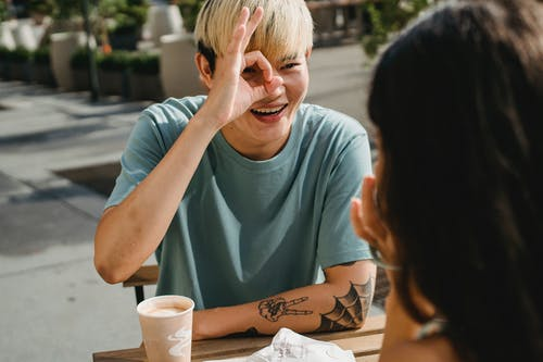 Happy young ethnic boyfriend smiling happily demonstrating ok sign to girlfriend while having coffee