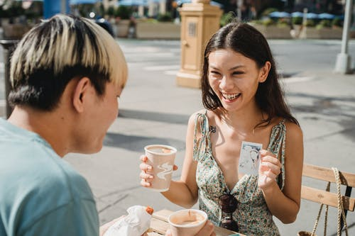 Cheerful ethnic female with cup of coffee showing photo made on instant photo camera while having lunch with boyfriend