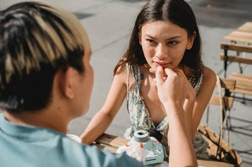 Crop anonymous male with dyed hair stroking hand of feminine ethnic beloved at table in street cafe while looking at each other