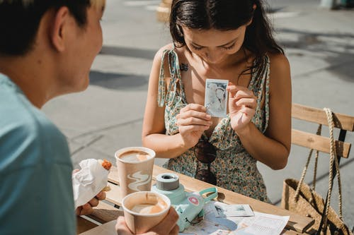 Crop woman showing photo to unrecognizable ethnic boyfriend on street