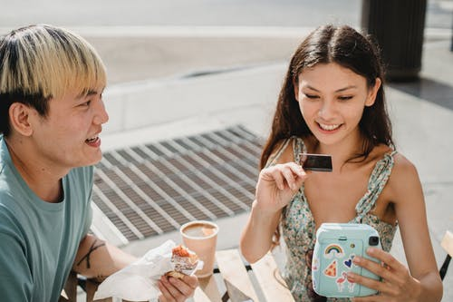 Crop smiling Asian man with cheerful ethnic girlfriend with photo camera at cafeteria table with takeaway coffee