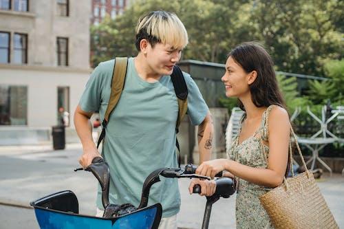 Heureux Jeune Couple Souriant Et Touchant La Bicyclette