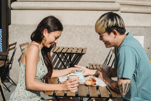 Young cheerful diverse couple holding hands and smiling