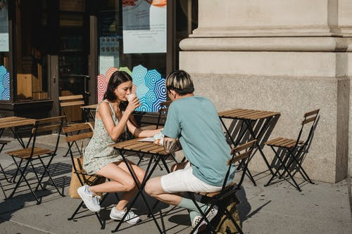 Serious friends drinking coffee while sitting at table on street on sunny day in summer