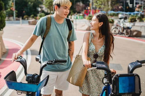 Calm multiracial friends standing with bicycles on street