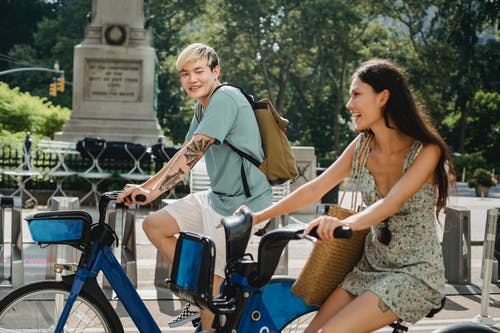 Side view of smiling Asian man riding bicycle with cheerful girlfriend in city in summertime