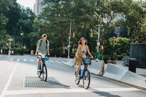 Cheerful couple riding bicycles on empty street