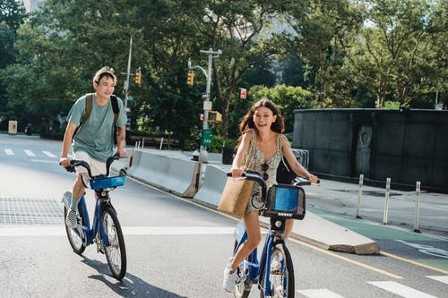 Cheerful diverse couple laughing and riding bicycles on asphalt road in city in sunny day