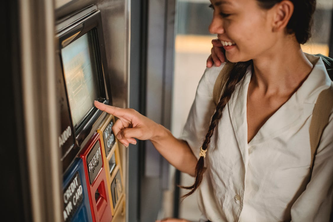 Crop smiling Asian female in white shirt using ticket vending machine with touch screen in underground