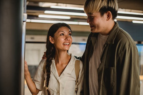 Cheerful Asian couple standing in underground station