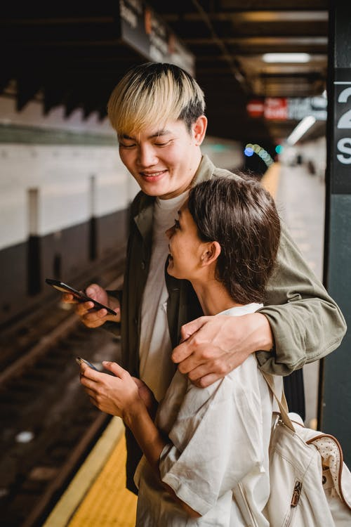 Happy young ethnic couple standing on platform of underground station with smartphones