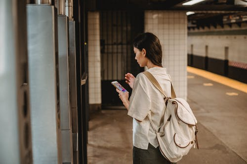 Side view of young concentrated ethnic female in casual clothes and backpack browsing mobile phone while standing on platform of subway station