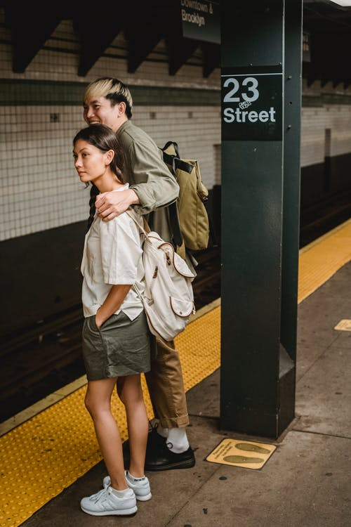 Full body of young ethnic couple standing on railway station platform