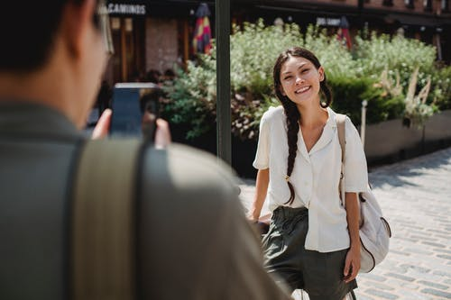 Anonymous guy photographing happy Asian girlfriend on smartphone on city street