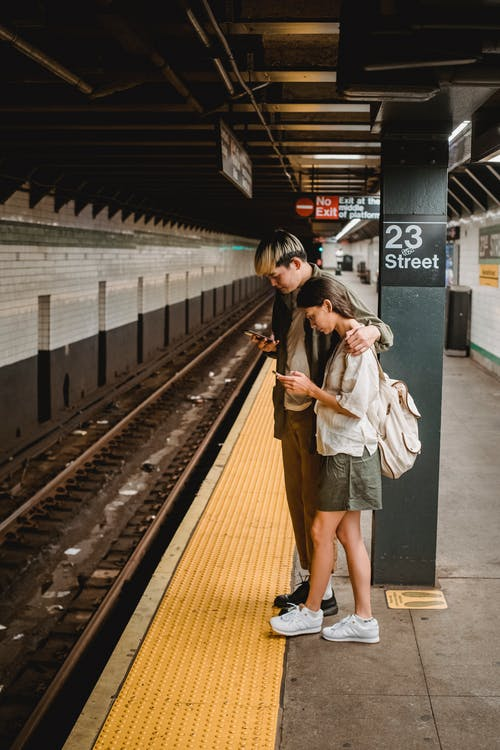 Side view of focused young ethnic couple in casual outfits using smartphones while waiting for train on railway station platform