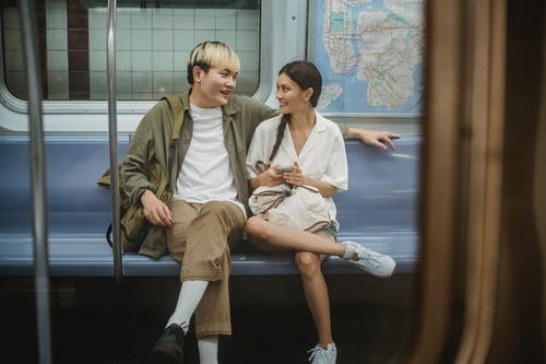 Happy young ethnic couple sitting in train and talking