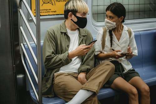 Unrecognizable young Asian man and ethnic woman in face masks and casual clothes using mobile phones and chatting while riding train