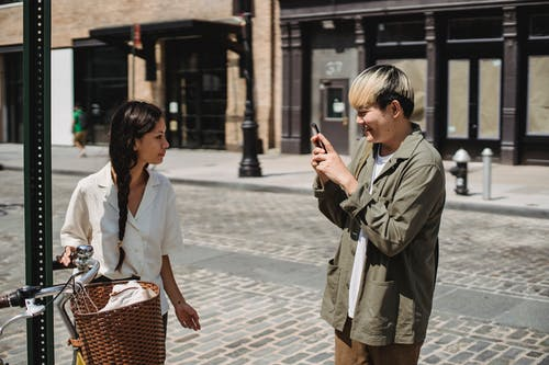 Happy ethnic man taking photo of girlfriend standing on street near bicycle