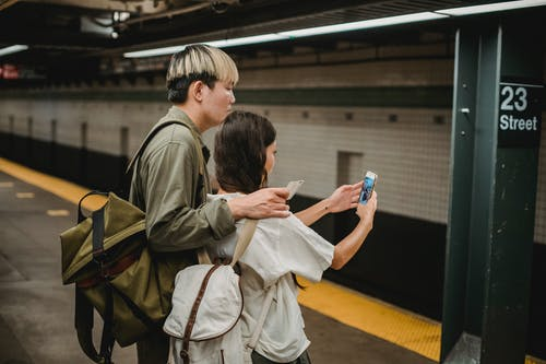 Side view of ethnic young female in casual clothes and backpack taking selfie with Asian boyfriend on smartphone while standing on platform in subway station