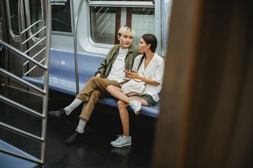 Full body of young stylish ethnic couple in casual clothes sitting in wagon while commuting by subway train