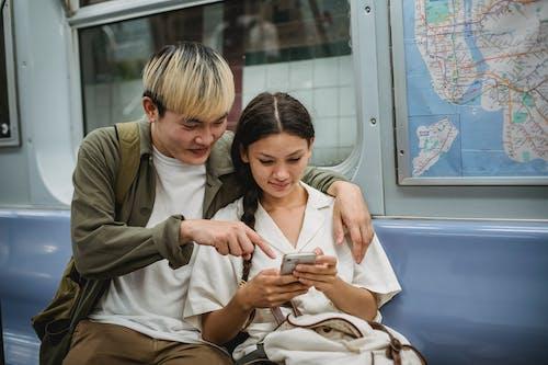 Pareja étnica Joven Positiva Abrazándose Y Usando Smartphone En Tren