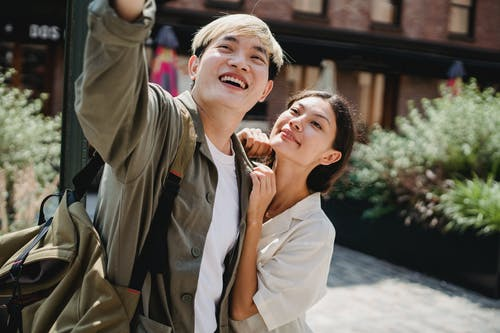Cheerful young Asian couple in trendy outfits cuddling and smiling while taking selfie on street during romantic holidays on sunny day