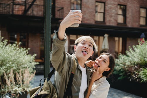 Happy young ethnic couple making funny grimace while taking selfie on smartphone