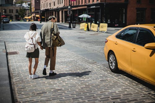 Anonymous couple catching taxi on street on sunny day