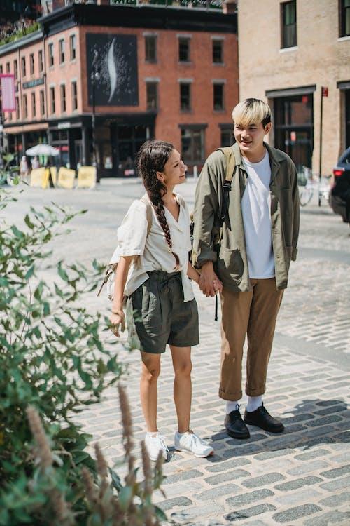 Jeune Couple Multiracial Positif Se Tenant La Main Et Marchant Sur Le Trottoir