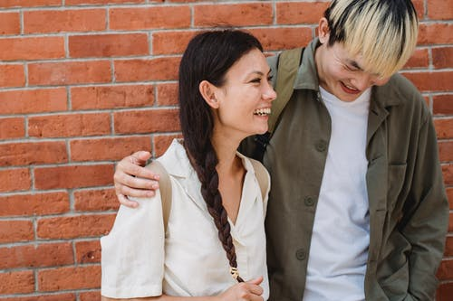 Positive young Asian couple cuddling while standing near brick wall