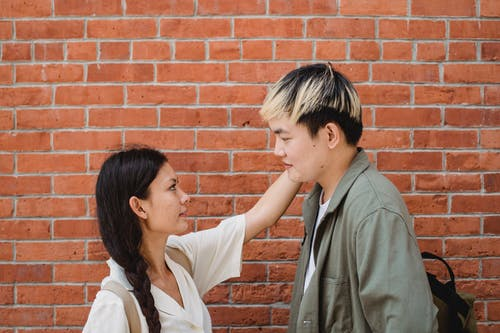 Loving ethnic couple standing near brick wall and looking at each other