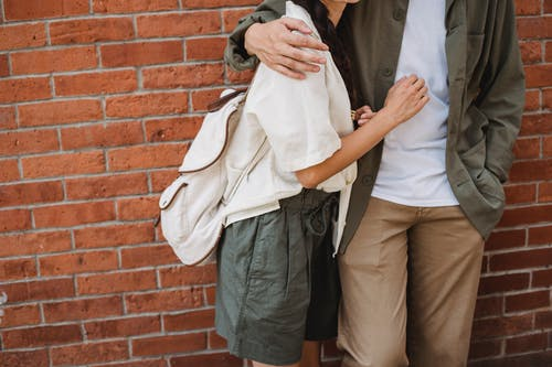 Crop faceless couple embracing against brick wall