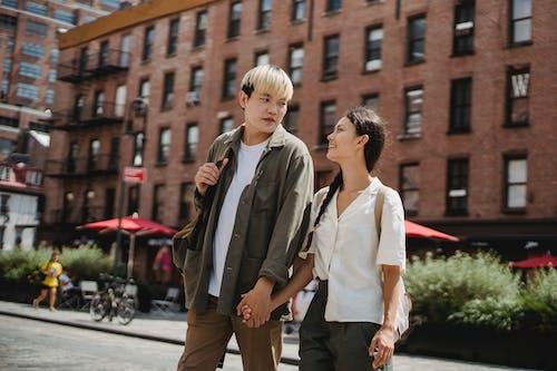 Cheerful Asian couple walking on sunny street