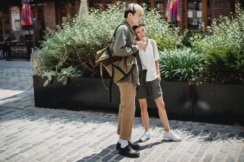 Positive Asian couple standing close on sunny street