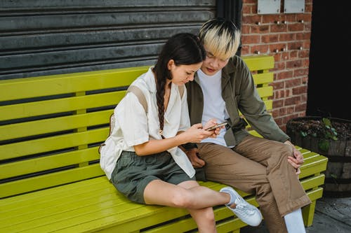 Content Asian couple in trendy outfits browsing modern mobile phone and sitting on wooden bench on street