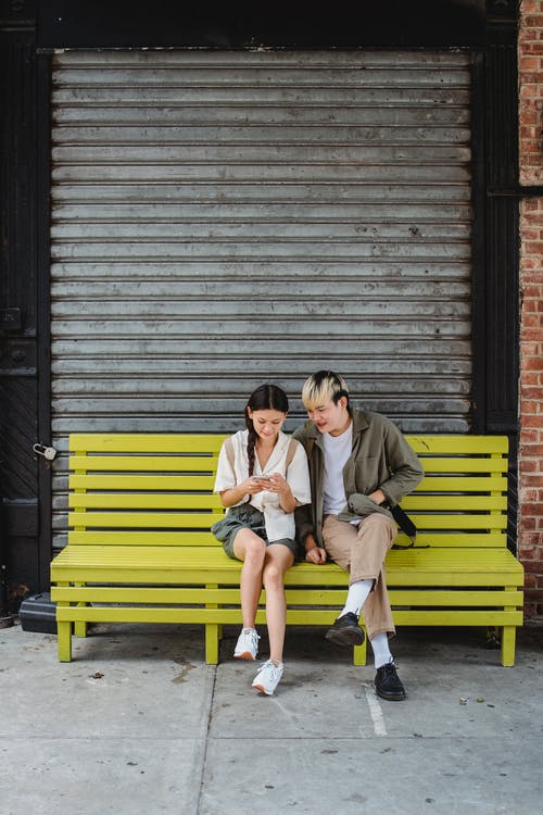 Calm multiracial friends in casual clothes sitting on wooden bench on street and looking at screen of smartphone in daytime