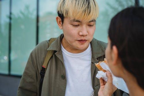 Woman hand feeding Asian boyfriend with hot dog