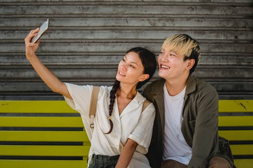 Smiling Asian couple taking selfie on smartphone on bench