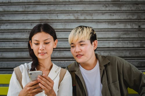 Content young Asian couple in casual outfits surfing contemporary mobile phones and sitting on street bench on clear weather