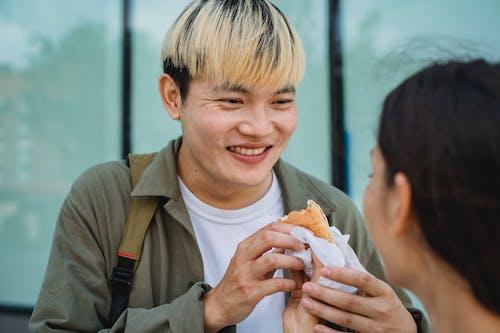 Crop woman hand feeding cheerful Asian boyfriend with hot dog