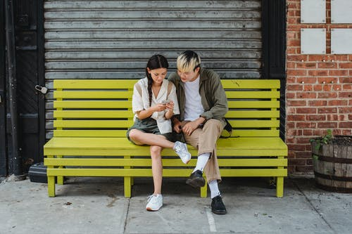 Serious multiracial couple resting on yellow bench and browsing smartphone and looking at screen