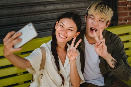 Delighted young Asian couple wearing casual clothes taking selfie on modern mobile phone and showing v sign while sitting on street bench
