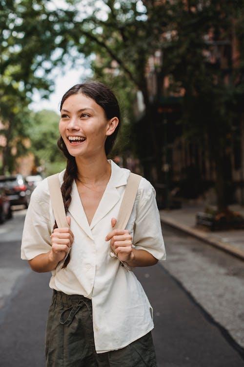 Joyful ethnic woman standing on sunny town street