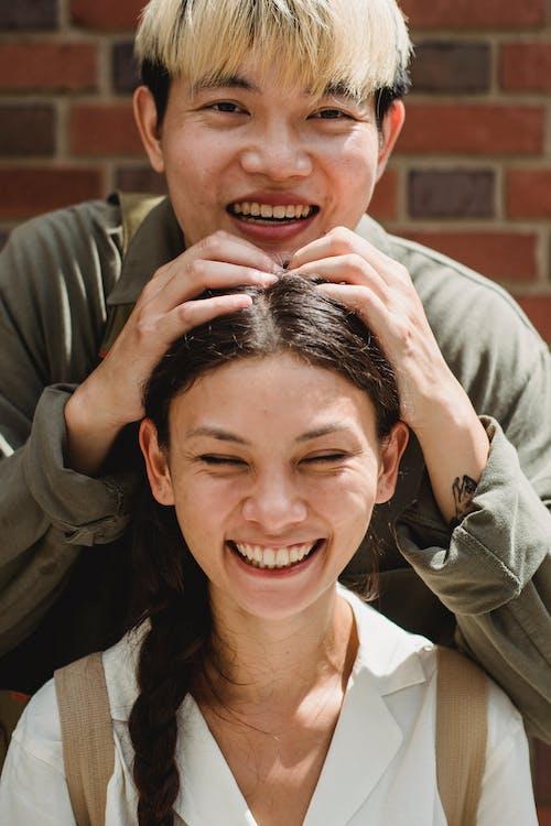 Joyful Asian man touching girlfriends head on sunny street