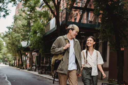 Cheerful multiethnic couple talking while walking on city street