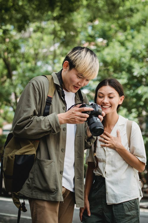 Young smiling diverse couple watching professional photo camera on street in town while spending time together on weekend