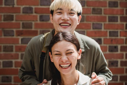 Crop smiling Asian man with dyed hair embracing laughing female beloved with closed eyes in sunlight