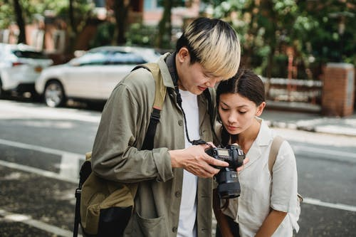 Multiracial couple sharing photo camera near road in town