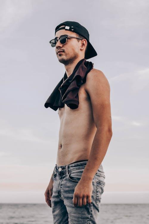 Confident shirtless man standing near water